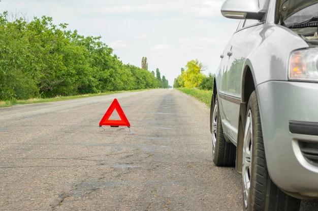 赤い緊急停止標識と道路上の壊れた銀車 Premium写真