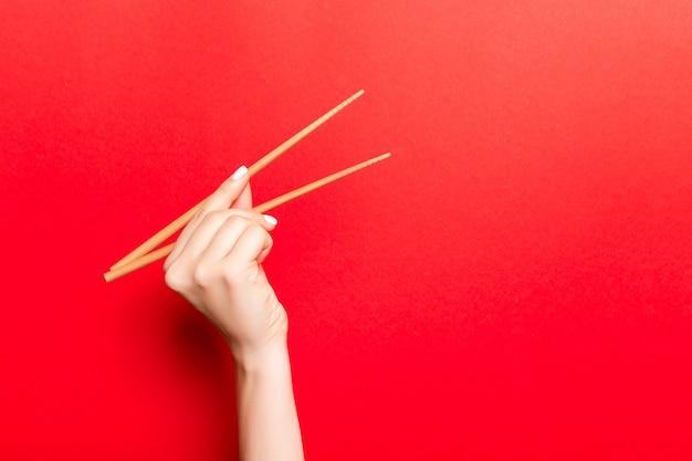 赤の背景に女性の手で木製の箸の創造的なイメージ。コピースペースを持つ日本料理と中華料理 Premium写真