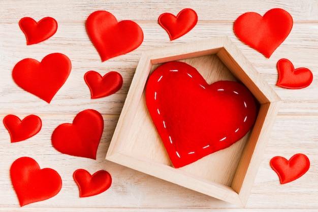木製の背景に小さな心に囲まれた家で赤いハートのトップビュー構成。ホームスイートホームコンセプト。バレンタイン・デー Premium写真