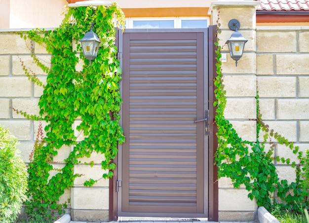 村の開いた空の下でモダンな納屋の白いレンガ。アイロンボルトとロック付きの木製のドアは、登山植物で生い茂っています。晴れた日の夏の田園風景 Premium写真