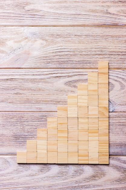 Куб деревянных блоков над черной деревянной текстурированной предпосылкой с космосом экземпляра для добавляет название текста слова. концептуальная или концептуальная лестница из деревянных блоков или девять ступеней. кубический Premium Фотографии