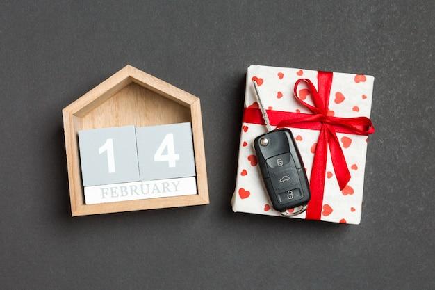 赤いハートとお祝いカレンダーのギフトボックスに車のキーのトップビュー Premium写真