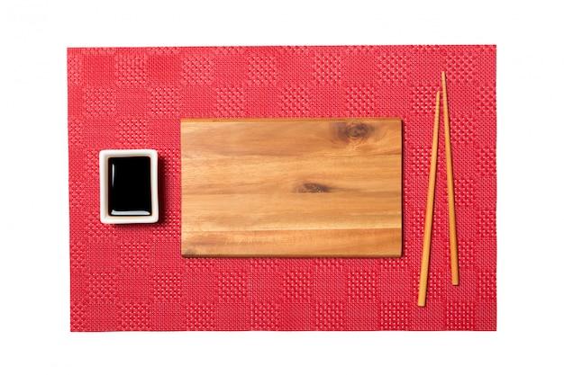 Опорожните прямоугольную коричневую деревянную плиту с палочками для суши и соевого соуса на красной предпосылке суши циновки. вид сверху с копией пространства для вашего дизайна Premium Фотографии