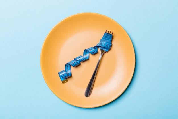 青の背景に丸皿にメジャーテープとフォークの平面図です。あなたのアイデアの空スペースで減量の概念 Premium写真