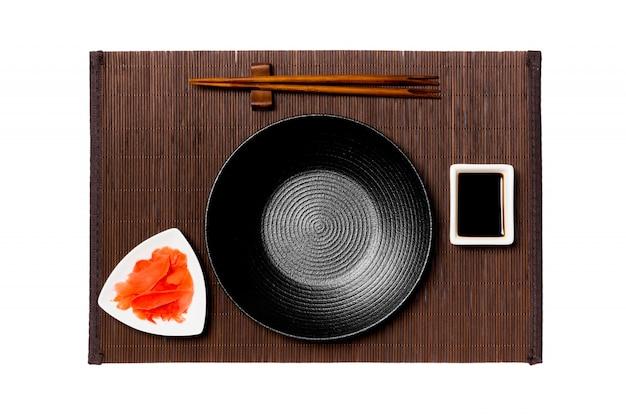 Пустая круглая черная тарелка с палочками для суши, имбиря и соевого соуса на бамбуковой циновке Premium Фотографии