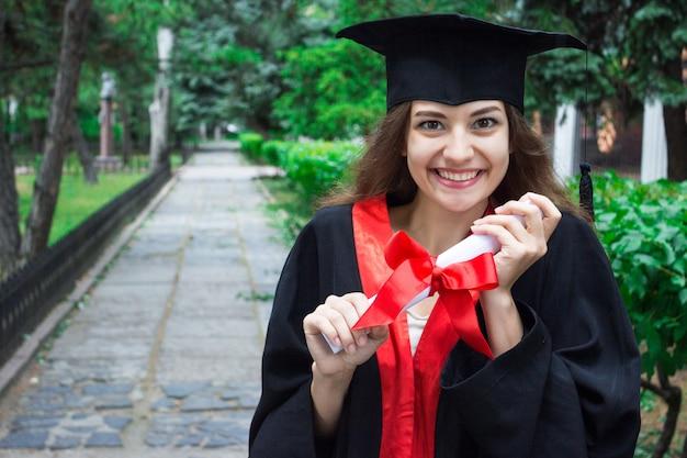 Женский портрет на ее выпускной день. университет. концепция образования, градации и людей Premium Фотографии