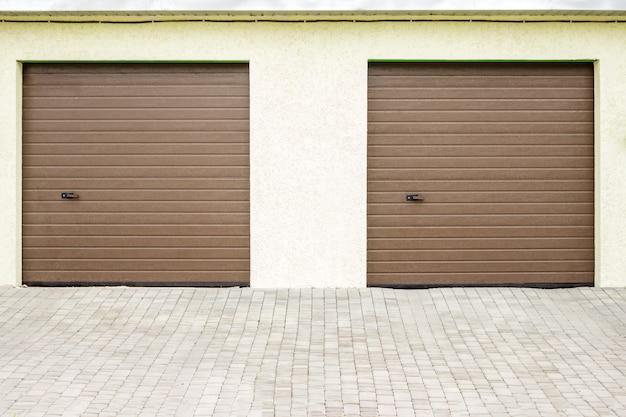 現代のガレージドアのペア。裕福な別荘のための大型自動アップガレージドア。 Premium写真