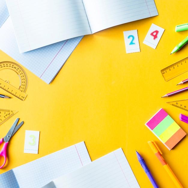 Тетради, ручки, карандаши, цифры и линейки на желтом фоне Premium Фотографии