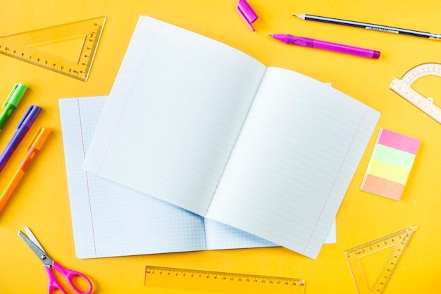 Тетради, ручки, карандаши и линейки на желтом фоне Premium Фотографии