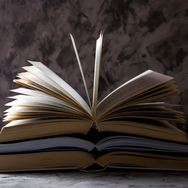 灰色の背景に裏返しのページで開いている本のスタック。 Premium写真