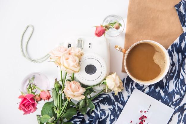 一杯のコーヒーの横にある花の中でデスクトップ上の白いカメラ。平面図、平干し Premium写真