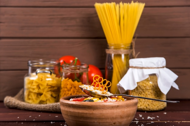 おいしい食べ物は皿の近くのスプーンにパスタが並んでいます Premium写真