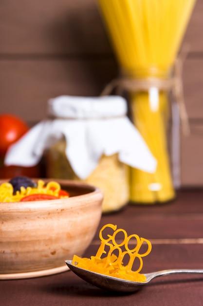 美味しい料理は、既製のパスタが入った皿の近くのスプーンにパスタが並んでいます Premium写真
