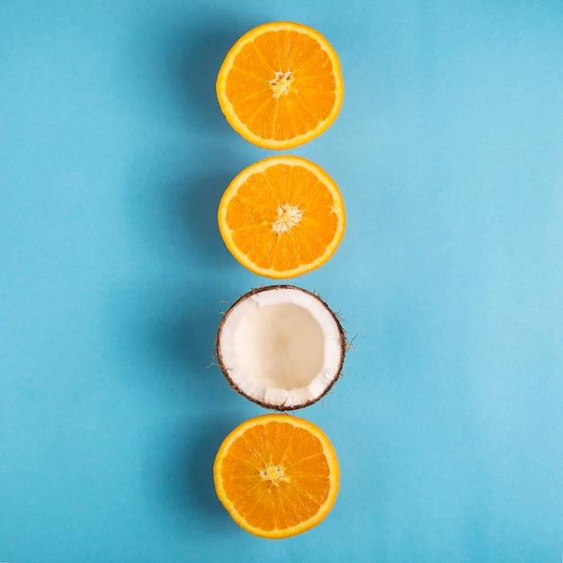 ジューシーな完熟オレンジと明るい青の背景にオープンココナッツ Premium写真