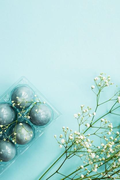青色の背景に石膏の花の中で繊細な青いイースターエッグ。 Premium写真