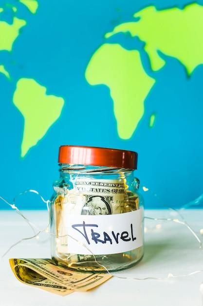 明るい世界地図の背景にドルとガーランドの旅行のための貯金箱。旅行のためのお金。蓄積の概念 Premium写真