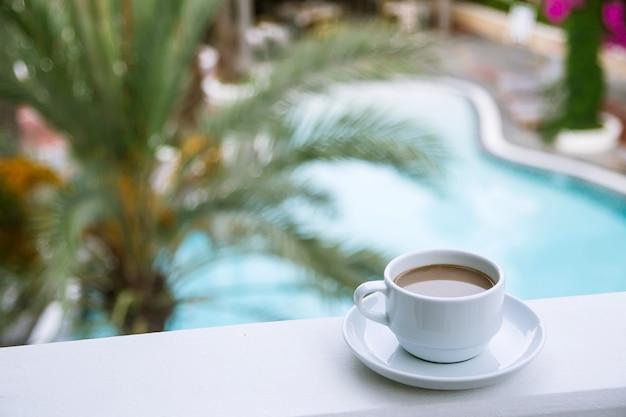 ホテルのバルコニーの白いカップにミルク入りのコーヒー。 Premium写真