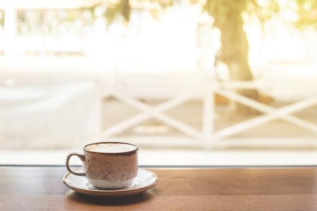 窓際のテーブルの上にあるカプチーノの小さなカップ。 Premium写真