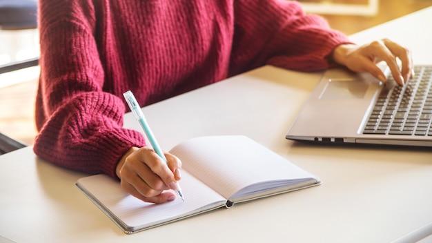 Девушка пишет в тетради и работает на своем ноутбуке на белом ...