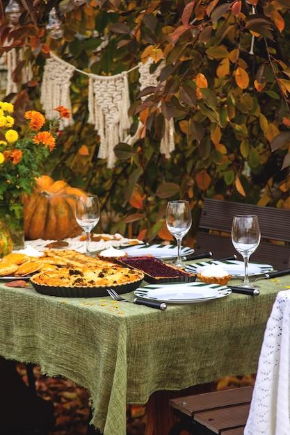 秋の裏庭で家族の休日のためのダイニングテーブル。 Premium写真
