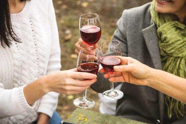 女性は秋の家族の夕食でワインとグラスをチャリンという音します。 Premium写真