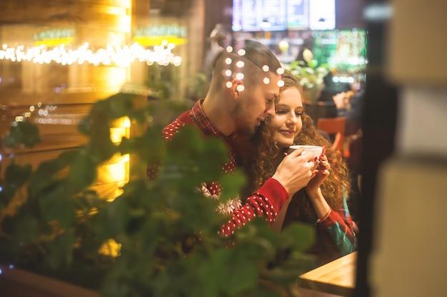 Парень и девушка сидят в кафе у окна. Premium Фотографии