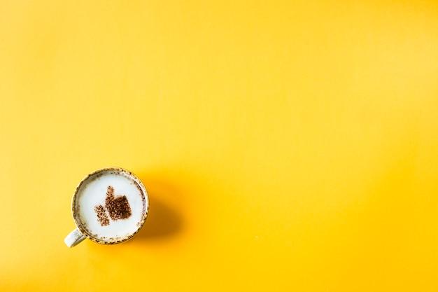 Чашка капучино, на которой нарисована улыбка, как большой палец вверх Premium Фотографии
