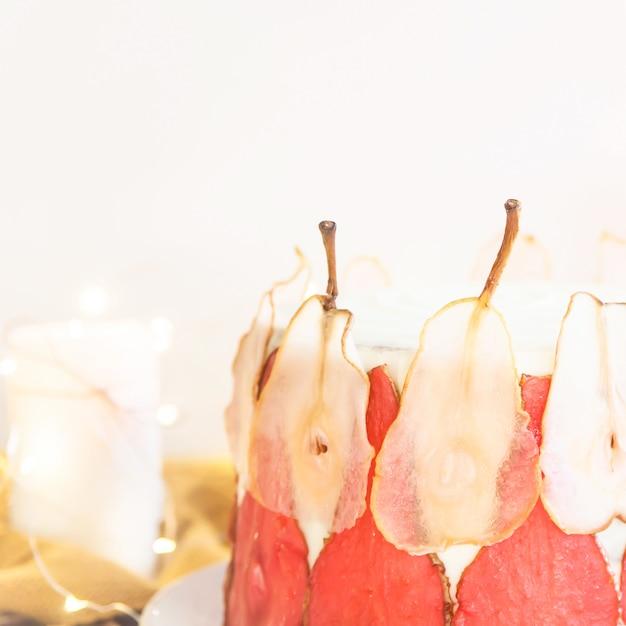 赤と白の洋ナシのスライスで飾られたお祝いの白いケーキ Premium写真