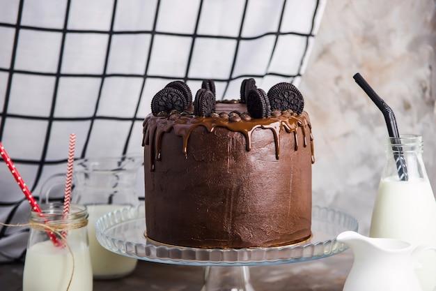 Шоколадный торт с печеньем на стеклянной подставке среди сосудов Premium Фотографии