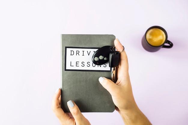 女性の手がレッスンを運転し、交通ルールと車のキーを勉強するためのトレーニング本を持っています Premium写真