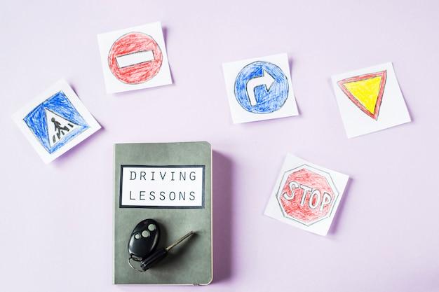 運転免許証を取得するための道路標識図面の横にある運転レッスンと運転規則の運転のためのトレーニングノート Premium写真