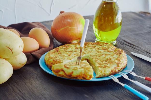 Испанский омлет с картофелем, яйцом и луком в сопровождении оливкового масла Premium Фотографии