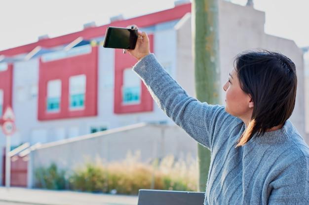 Молодая девушка разговаривает по смартфону и печатать сообщения с смартфона Premium Фотографии