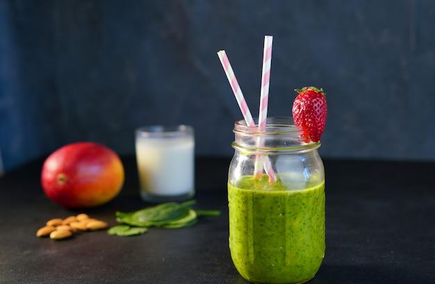 健康的なグリーンリーチビタミンスムージー、ベビーリーフほうれん草、マンゴー、アーモンドミルク、ストロベリー Premium写真