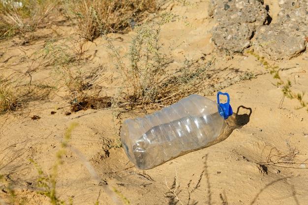 空のペットボトルは砂の上にあります Premium写真