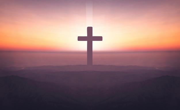 十字架のシルエットは、聖と光の背景を持つ日没時に山の上をクロスします。 Premium写真