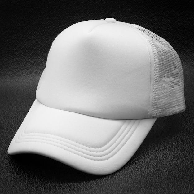 暗い背景に白い帽子。デザインのファッション帽子。 Premium写真