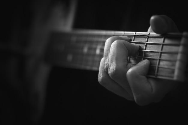 アコースティックギターの背景を演奏する手のクローズアップ。 Premium写真