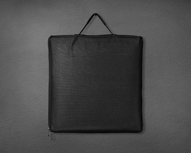 セメントの背景に黒い布バッグ。 Premium写真