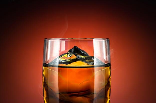 ウイスキーと赤の背景に氷のグラス。冷たい飲み物とアルコールのガラスのクローズアップ。 Premium写真