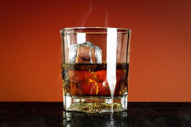 赤のウイスキーとアイスキューブのガラス Premium写真