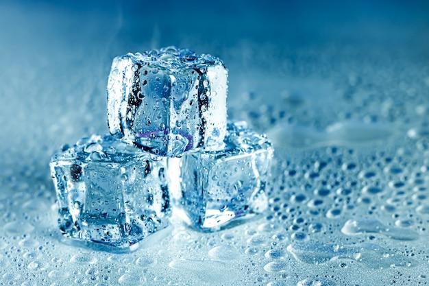 アイスキューブと水はクールな背景に溶けます。冷たい飲み物や飲み物と氷のブロック。 Premium写真