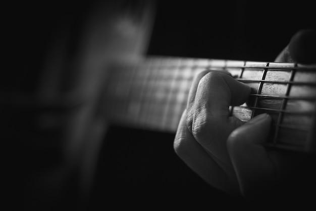 Закройте вверх руки играя акустическую гитару в предпосылке памяти. Premium Фотографии