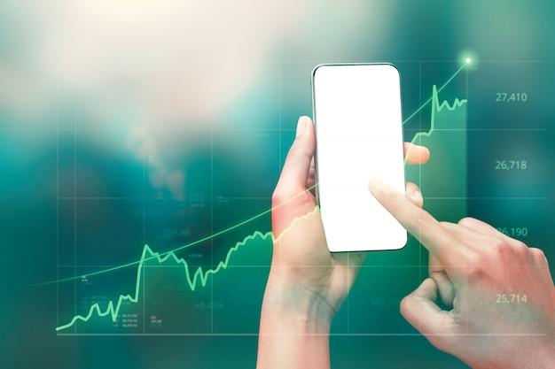 Бизнесмен держа смартфон и показывая голографические диаграммы и статистику фондовой биржи получает прибыль. Premium Фотографии