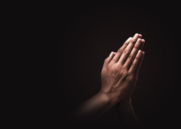 暗闇で宗教と神への信仰を信じて祈る。希望または愛と献身の力。ナマステまたはナマスカーの手ジェスチャー。祈りの位置。 Premium写真
