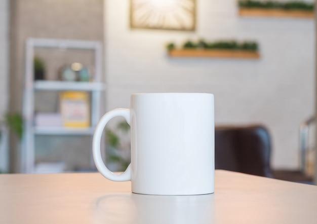 Белая кружка на столе и фоне современной комнаты Premium Фотографии