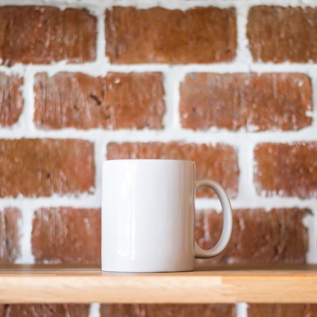 ビンテージレンガ壁の背景に白のマグカップ Premium写真