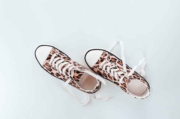 Модные белые кроссовки с принтом животных на светло-сером фоне Premium Фотографии