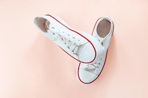 Белые модные белые кроссовки на кремово-персиковом фоне. плоская планировка, вид сверху. место для текста. минималистичный стиль композиции. Premium Фотографии