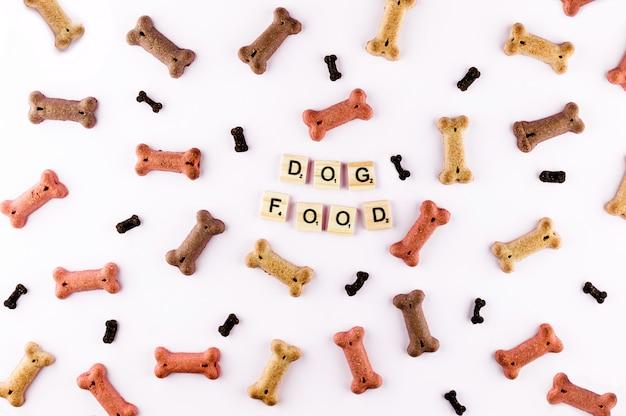 骨の形をしたドライスナックで作られたドッグフードパターン。木製のタイルの単語犬。 Premium写真